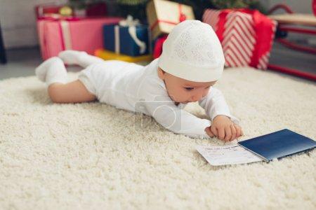 Photo pour Mignon petit bébé avec billet d'avion et passeport couché sur le sol avec des cadeaux de Noël flous sur fond - image libre de droit