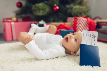 happy little baby with flight ticket and passport lying on floor with christmas tree blurred on background