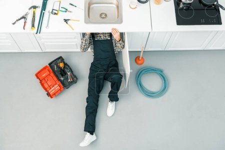 high angle view of plumber lying on floor and checking sink in kitchen