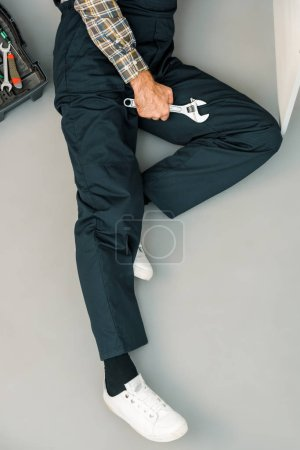 cropped image of plumber lying on floor with adjustable wrench in kitchen