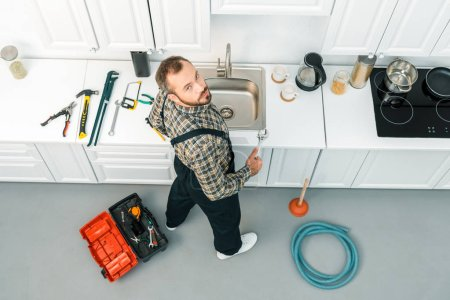 Photo for High angle view of handsome plumber holding adjustable wrench and looking at camera in kitchen - Royalty Free Image