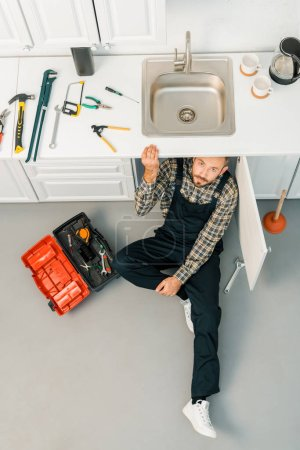 high angle view of handsome plumber sitting on floor near sink and looking at camera in kitchen