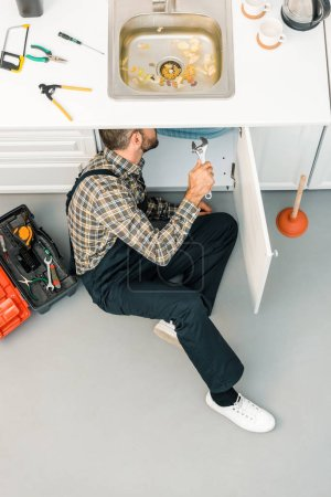 high angle view of plumber repairing sink with adjustable wrench in kitchen