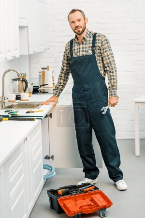 handsome plumber holding adjustable wrench and looking at camera in kitchen