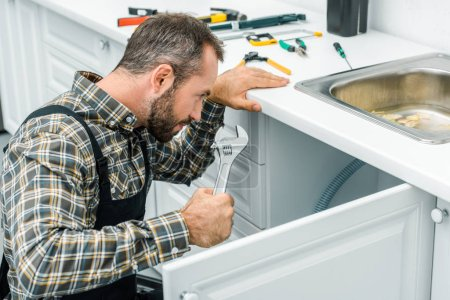 bearded repairman holding adjustable wrench and looking under broken sink in kitchen