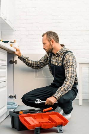 side view of handsome repairman holding adjustable wrench and looking under broken sink in kitchen