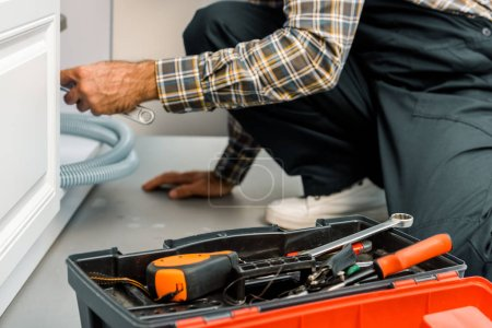 cropped image of plumber repairing broken sink in kitchen