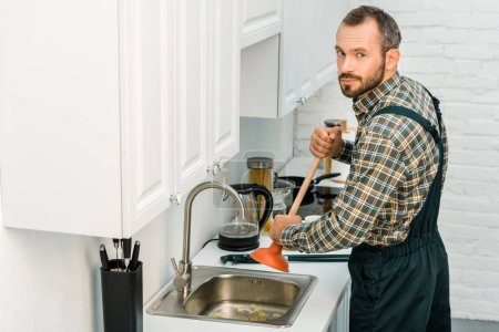 handsome plumber using plunger and cleaning sink in kitchen, looking at camera