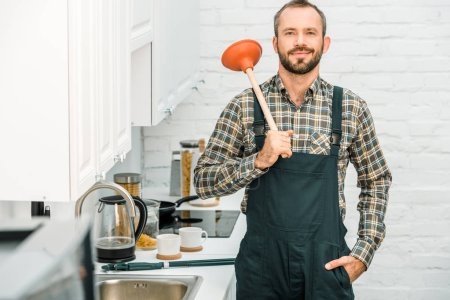 Photo for Cheerful handsome plumber holding plunger on shoulder and looking at camera in kitchen - Royalty Free Image