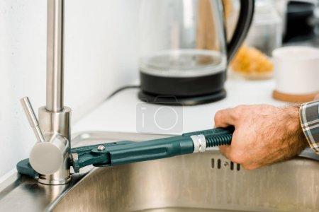 Photo for Cropped image of plumber repairing tap with monkey wrench in kitchen - Royalty Free Image