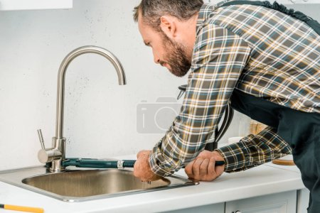 handsome plumber repairing tap with monkey wrench in kitchen