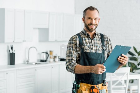 Photo for Smiling handsome plumber holding clipboard and looking at camera in kitchen - Royalty Free Image
