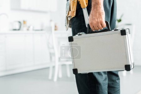 cropped image of plumber holding toolbox in kitchen