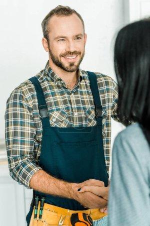 Photo pour Souriant, beau plombier et client se serrant la main dans la cuisine - image libre de droit