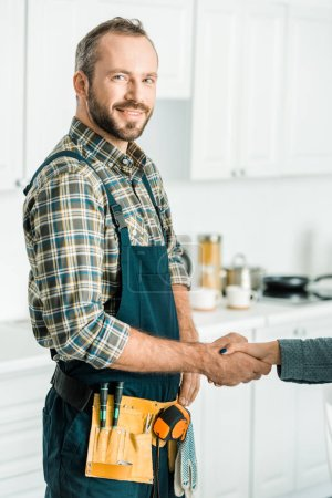 smiling handsome plumber and customer shaking hands in kitchen