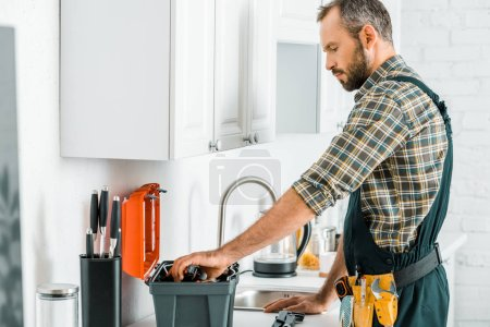 Photo for Side view of handsome plumber taking tools from toolbox in kitchen - Royalty Free Image
