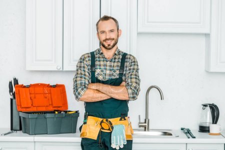 Photo for Smiling handsome plumber standing with crossed arms and looking at camera in kitchen - Royalty Free Image