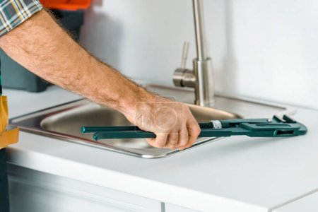 cropped image of plumber holding monkey wrench near sink in kitchen