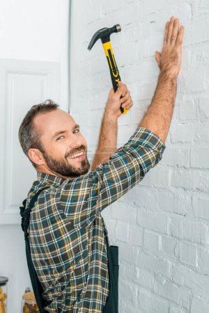 smiling handsome repairman hammering nail in white wall and looking at camera