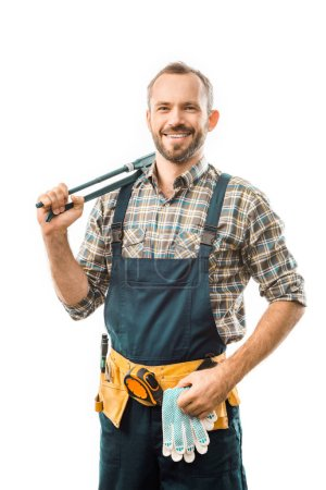 smiling plumber with tool belt holding monkey wrench and looking at camera isolated on white
