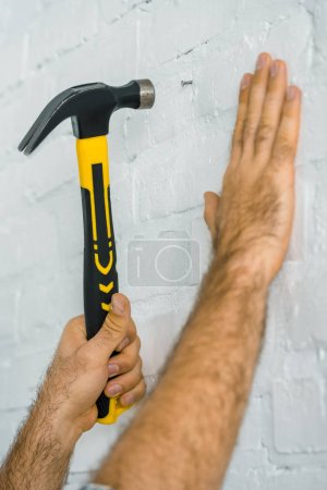 cropped image of repairman hammering nail in white wall