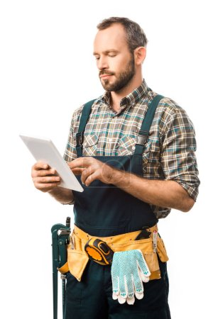 handsome plumber with tool belt using tablet isolated on white