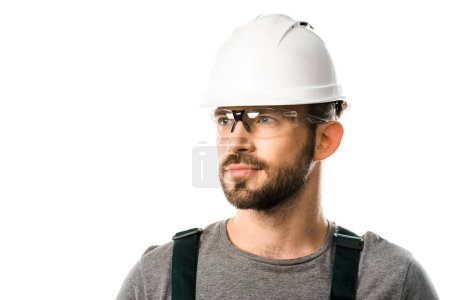 portrait of handsome plumber in helmet and protective glasses looking away isolated on white