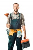 smiling handsome plumber holding plunger and toolbox isolated on white, looking at camera