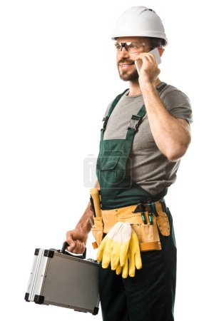 Photo for Handsome electrician talking by smartphone and holding toolbox isolated on white - Royalty Free Image
