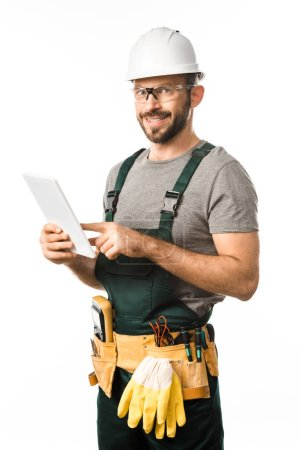 smiling handsome electrician in helmet and protective glasses using tablet isolated on white