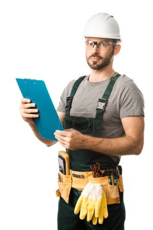 handsome electrician with tool belt holding clipboard and looking at camera isolated on white