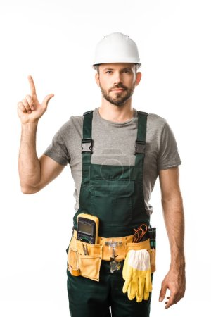 handsome electrician with tool belt pointing up isolated on white