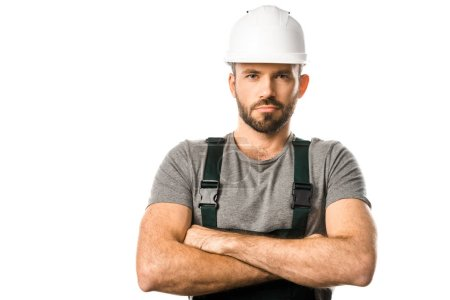 Photo pour Beau plombier dans le casque debout avec les bras croisés et regardant la caméra isolée sur blanc - image libre de droit