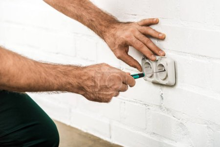 cropped image of electrician repairing power socket with screwdriver at home