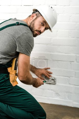 handsome electrician repairing and unscrewing power socket with screwdriver at home, looking at camera