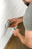 cropped image of electrician repairing and unscrewing power socket with screwdriver at home
