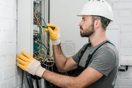 Foto de Vista lateral del apuesto electricista barbudo reparar caja eléctrica y con destornillador en corredor - Imagen libre de derechos