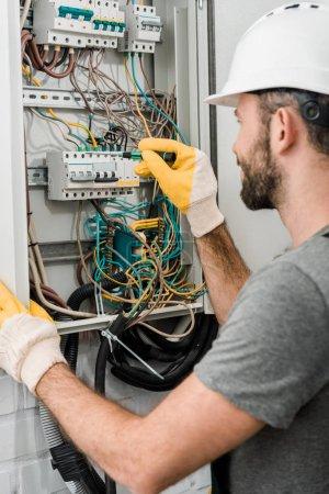 Photo pour Vue latérale d'électricien réparant la boîte électrique et en utilisant le tournevis dans le couloir - image libre de droit