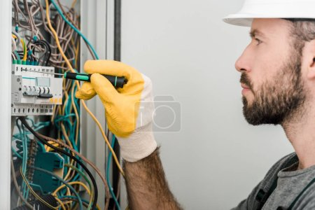 Photo for Side view of handsome electrician repairing electrical box and using screwdriver in corridor - Royalty Free Image