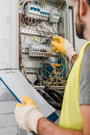 cropped image of electrician holding clipboard and inspecting electrical box in corridor