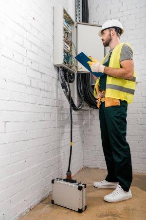 Foto de Vista de ángulo bajo de electricista guapo sosteniendo portapapeles y comprobación de caja eléctrica en el corredor - Imagen libre de derechos