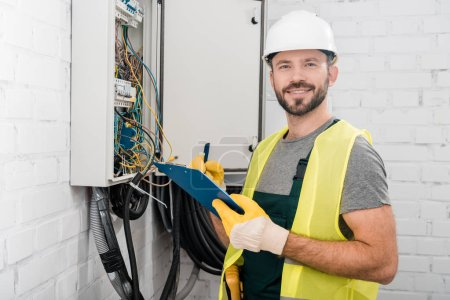 Photo for Smiling handsome electrician holding clipboard near electrical box in corridor and looking at camera - Royalty Free Image