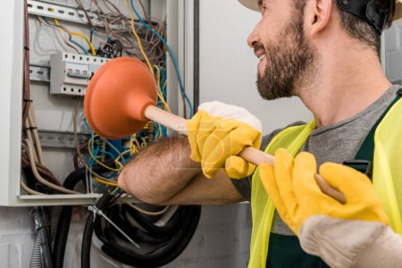 Photo for Smiling electrician repairing electrical box with plunger in corridor - Royalty Free Image