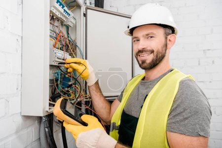 Photo for Smiling handsome electrician checking electrical box with multimetr in corridor and looking at camera - Royalty Free Image