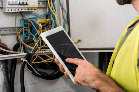 cropped image of electrician using tablet near electrical box in corridor