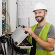 Smiling electrician holding toolbox near electrica...