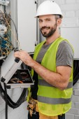 smiling handsome electrician holding toolbox near electrical box in corridor and looking at camera