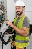 souriant toolbox tenue beau électricien près de boîte électrique dans le couloir et regardant la caméra