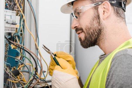 Photo pour Vue latérale du beau électricien détenant une pince et en regardant une boîte électrique dans le couloir - image libre de droit