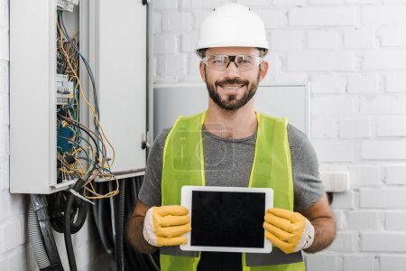 smiling handsome electrician showing tablet with blank screen near electrical box in corridor